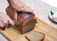 Coupure du pain brun Images stock