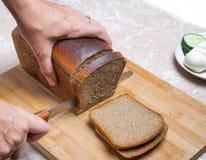 Coupure du pain brun Images libres de droits