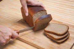 Coupure du pain brun Photo stock