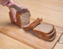 Coupure du pain brun Photographie stock