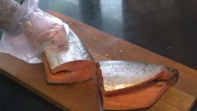 Coupure du poisson de mer delicatessen Fruits de mer Le poisson est coupé sur une planche à découper banque de vidéos