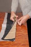 Coupure du tissu dans l'atelier avec des ciseaux Images libres de droits
