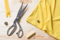 Coupure du tissu jaune avec des ciseaux d'un Taylor sur la table en bois Photos stock