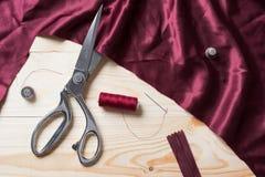 Coupure du tissu marron avec des ciseaux d'un Taylor sur la table en bois Photos stock
