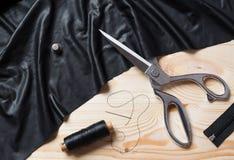 Coupure du tissu noir avec des ciseaux d'un Taylor sur la table en bois Photos libres de droits