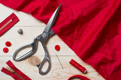 Coupure du tissu rouge avec des ciseaux d'un Taylor sur la table en bois Photo stock