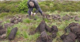 Coupure et tourbe convenable de gazon avec une pelle en marais de mousse en Irlande banque de vidéos