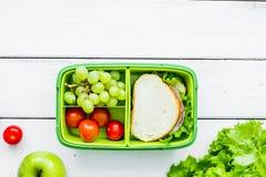 Coupure saine avec la pomme, le raisin et le sandwich dans le panier-repas sur la maison Images libres de droits