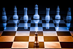 Courage. Black pawn alone against a lot of white pieces royalty free stock photo