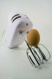 Courage. A brown egg climbing up a mixer stock photography