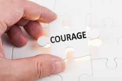 Courage concept. Hand holding puzzle piece which written courage word and inserting it into group of white paper jigsaw puzzles stock photos