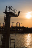 Courage and Jump: Success Abstract Concept. Courage and Jump: Silhouette of Child Jumping from High Board into Water, Fun in the Summer Royalty Free Stock Photos