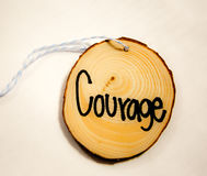 Courage. Round piece of wood on a string with the word Stock Photography