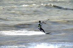 The courage to conquer the waves. Sochi, Russia, on 28 April 2016. The man is engaged in kitesurfing in the sea Stock Image