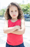 Courageous child in a red shirt outside looking at camera. Outside in the city Royalty Free Stock Photography