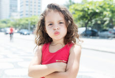 Courageous child in a red shirt outside looking at camera. With green plants and buildings in the background Stock Photos