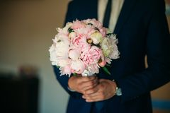 The courageous groom dresses his wedding suit. He holds a bouquet in his hands. Wedding day.  Stock Images