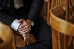 Courageous hands with the groom`s. Watch who expects his bride on a wooden chair Stock Image