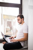The courageous, handsome, a student working on a windowsill with a laptop. worker communicating on the Internet. Funny man play for laptop Royalty Free Stock Photo