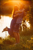 Courageous man in hat holding his brunette wife on hand, smiling and looking each other. Romantic atmosphere on pier of lake at su Royalty Free Stock Images
