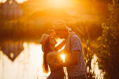 Courageous man in hat holding his brunette wife on hand, smiling and looking each other. Romantic atmosphere on pier of lake at su Stock Photography