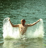 Courageous muscular man in the lake playing with the water Royalty Free Stock Photos
