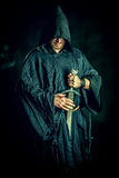 Courageous. Portrait of a courageous warrior wanderer in a black cloak and sword in hand. Historical fantasy Stock Image