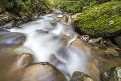 Courant fluide de rivière avec de l'eau soyeux lisse tombant de grandes pierres en belles cascades le jour ensoleillé lumineux d' images stock