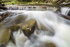 Courant fluide de rivi?re avec de l'eau soyeux lisse tombant de grandes pierres en belles cascades le jour ensoleill? lumineux d' images stock