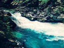 Courant transparent bleu de montagne parmi des roches images stock
