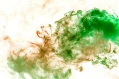 Courants minces de fumée grise teintés en vert sur un fond blanc comme la dissolution d'aquarelle photo stock
