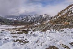 Courbe d'épingle à cheveux de route de neige de montagnes Photos stock