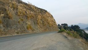 Courbe dans la route Dégagement de saleté de bord de la route Courbe de côté de falaise d'océan photographie stock