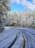 Courbe sur Milou, route glaciale avec des voies de pneu Images stock