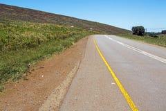 Courber la route d'Ashphalt avec les lignes jaunes et blanches photo libre de droits