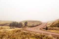 Courber la route rouge dans un Oklahoma brumeux images stock