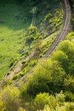 Courber la voie de chemin de fer par une forêt photo stock