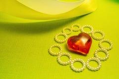 Courber le ruban et le coeur en verre sur un fond vert, une déclaration de l'amour et des félicitations Image stock