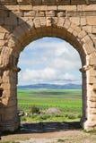 Courbez chez Volubilis, ville romaine antique au Maroc Photos stock
