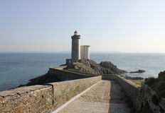 Courbez la route au phare dans la Bretagne, France Images libres de droits