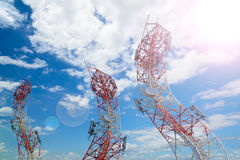 Courbez la tour d'antenne de communication de téléphone portable avec le ciel bleu Image stock