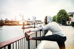 Coureur d'homme de couleur avec le smartphone dans un brassard sur le pont dans une ville, s'étendant photo libre de droits