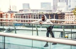 Coureur d'homme de couleur avec le smartphone dans un brassard sur le pont dans une ville, s'étendant photo stock