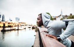 Coureur d'homme de couleur avec le smartphone dans un brassard sur le pont dans une ville, se reposant photos stock