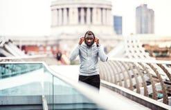 Coureur d'homme de couleur avec le smartphone dans un brassard sur le pont dans une ville, se reposant photographie stock