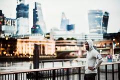 Coureur d'homme de couleur avec le smartphone dans un brassard sur le pont dans une ville, se reposant image libre de droits