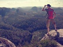 Coureur d'itinéraire aménagé pour amateurs de la nature dans le T-shirt et shorts observant le matin paresseux photo stock