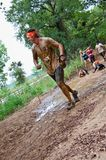 Coureur de course de boue passant le puits de boue Images libres de droits
