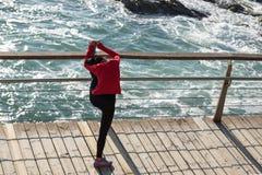 Coureur de femme étirant des jambes sur la promenade de bord de la mer images libres de droits