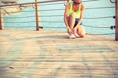 Coureur de femme de forme physique attachant la dentelle à la promenade de bord de la mer Photo stock